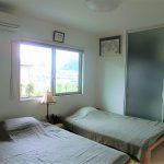 壁掛けテレビ付きの寝室。奥には収納スペース(寝室)
